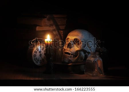 Still life with skull, old books and candle - stock photo