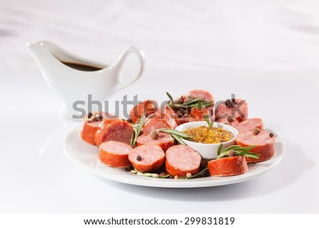 still life with sliced sausage, pepper, rosemary, sauce and mustard. on a white background
