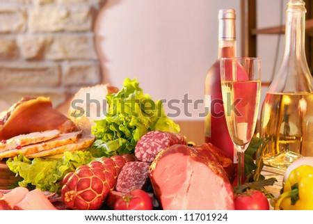 Still-life with smoked pork, sausage, green salad and wine. - stock photo