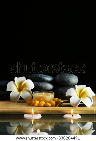 Still life with spa stones on black background - stock photo