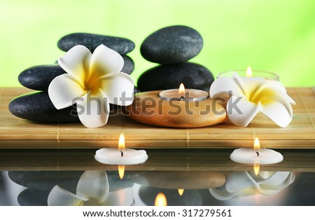 Still life with spa stones on green blurred background - stock photo