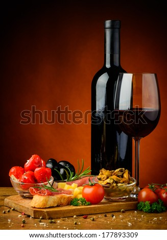 still life with spanish tapas, glass and bottle of red wine - stock photo