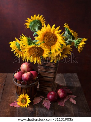 Still life with Sunflowers and apples on old wooden table - stock photo