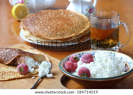 Still-life with tea a fresh strawberry and pancakes with cottage cheese, berries of a fresh juicy sweet strawberry and appetizing pancakes with rural cottage cheese and fragrant fresh tea - stock photo