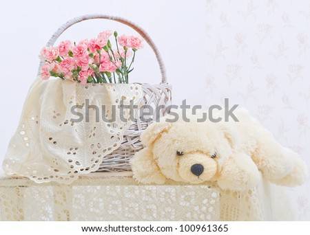 Still life with teddy bear, wicker basket and pink flowers - stock photo