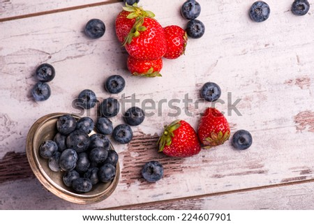 Still life with the copper top and little blackberries in it scattering on the wooden table amid the tempting red strawberries. Top view - stock photo