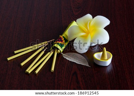 Still-life with the flower shaped candle and aroma sticks - stock photo