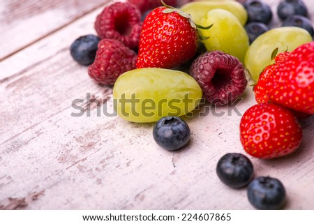 Still life with the tempting raspberry lying among the scattering blackberry and delicious grape on the wooden table - stock photo