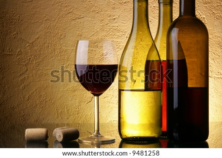 Still-life with three wine bottles and glass over textured background - stock photo