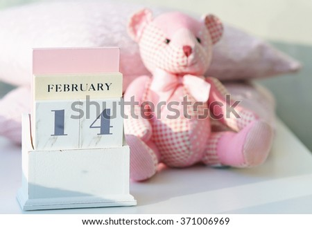 Still life with toy bear and table calendar set on Valentine's Day