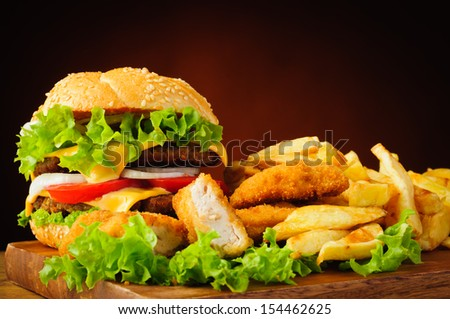 still life with traditional cheeseburger, fried chicken nuggets and french fries - stock photo