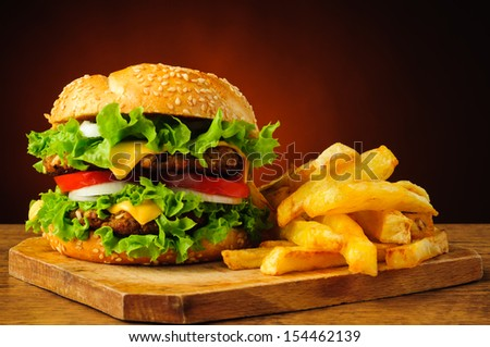 still life with traditional hamburger and french fries - stock photo