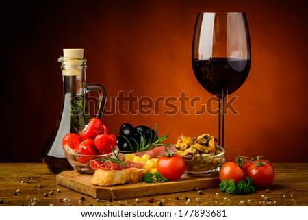 still life with traditional tapas snack and glass of red wine - stock photo
