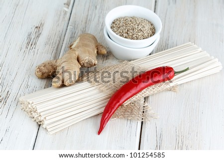 Still life with udon noodles, ginger, sesame seed and chili pepper. - stock photo