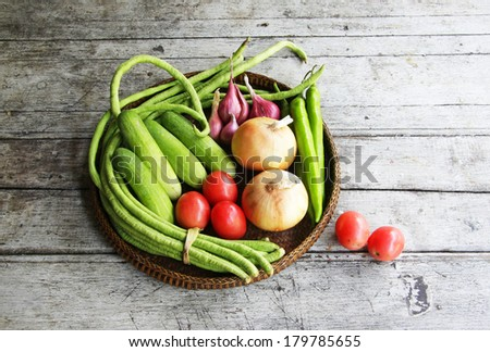 still life with vegetables on a wooden ,cow pea, red onion, cucumber,tomato and onions.  - stock photo