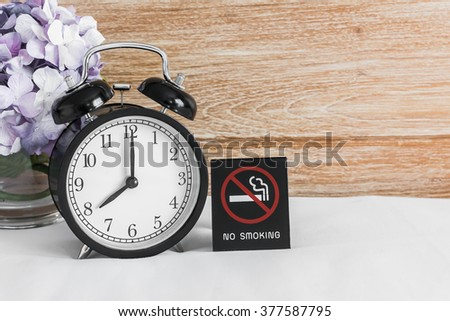 Still life with vintage alarm clock, flower and no smoking sign displayed on bed over wood background ( alarm clock show 8 o`clock ) - stock photo