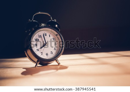 Still life with vintage alarm clock on leather.( alarm clock show 8 o`clock )