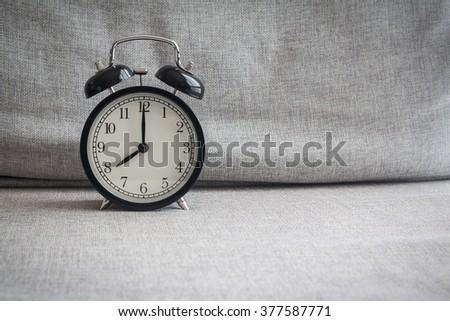Still life with vintage alarm clock on sofa ( alarm clock show 8 o`clock ) - stock photo
