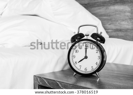 Still life with vintage alarm clock on table in bedrood ( alarm clock show 8 o`clock ) - stock photo