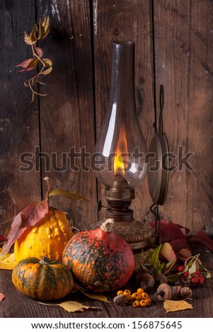 Still life with vintage burning lamp with colorful pumpkins, acorns and autumn leaves on old wooden table - stock photo