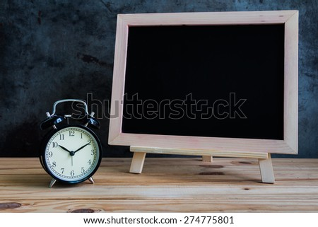 Still life with vintage clock and empty chalkboard on wooden table over grunge background