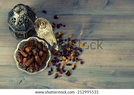 Still life with vintage oriental latern, raisins and dates on wooden background. retro style toned picture - stock photo