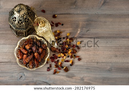 Still life with vintage orintal latern, raisins and dates on wooden background - stock photo