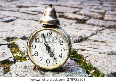 still life with vintage retro alarm clock with old brick wall background - stock photo
