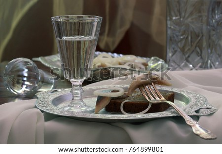 still life with vodka and a sandwich with herring and onion