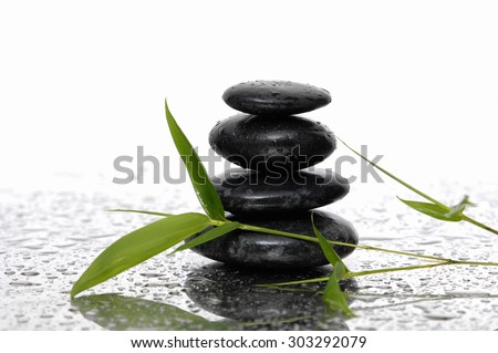 Still life with wet stacked stones with bamboo - stock photo