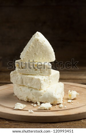 Still life with white cheese on wooden board - stock photo