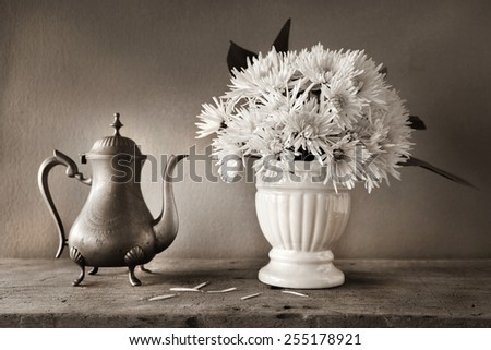 Still life with white dahlias in vase and brass tea pot on wooden table - stock photo