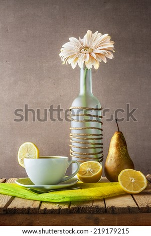 Still life with white gerbera in a bottle and tea - stock photo