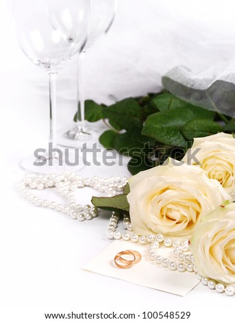 Still life with white roses, pearls and wedding rings - stock photo