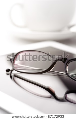 Still life with white tablet, coffee cup and glasses on a white table - stock photo