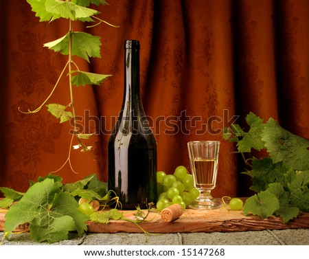 Still life with white wine and brown drapery on background - stock photo