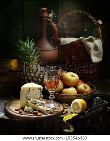 Still-life with white wine and fruit, fragrant cheese with fresh sweet ripe apples juicy pineapple fried almonds and a white wine wine glass - stock photo