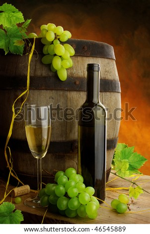 Still life with white wine with fresh grapevine and old cask - stock photo