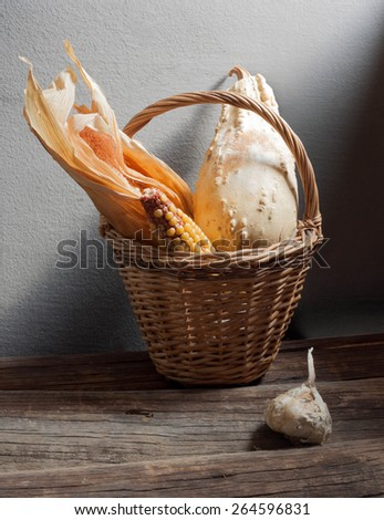 still life with wicker basket, corn, garlic, pumpkin, zucchini - stock photo