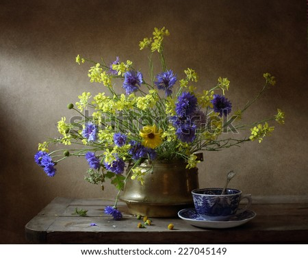 Still life with wild flowers and a cup of tea - stock photo