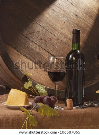 Still life with wine barrel, bread and cheese - stock photo