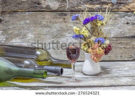 Still life with wine  bottle, dry little flower on wood table background - stock photo