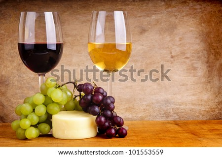 still life with wine, cheese and grapes on a wooden background with copy space