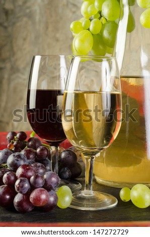 Still life with wine glasses, wine bottles and grapes - stock photo