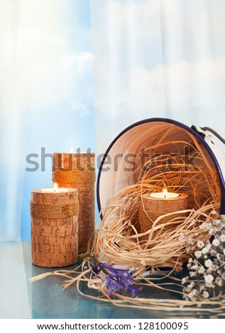 still life with wooden candle holders,candles,straw,flowers and a vintage bucket - stock photo