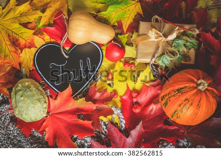 Still life with wrapped gift, colorful dry leaves, small red apples and fall inscription