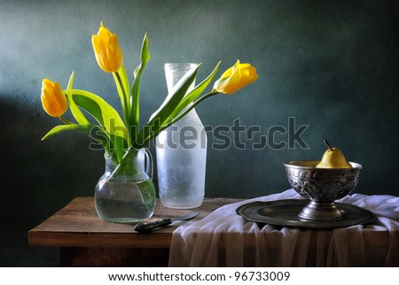 Still life with yellow tulips and pears - stock photo