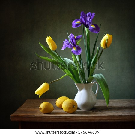 Still life with yellow tulips, irises and lemons - stock photo