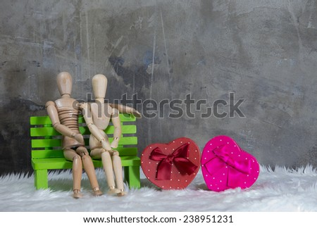 Still life, Wooden puppet men women sit on chairs, and gift boxes. - stock photo