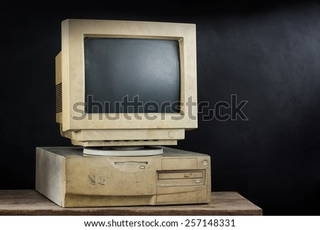 still photography : old and obsolete computer on old wood with art dark background - stock photo